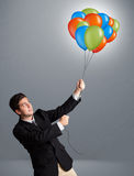 Handsome man holding colorful balloons Royalty Free Stock Images