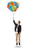 Handsome man holding colorful balloons Stock Images