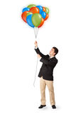 Handsome man holding colorful balloons Stock Photography