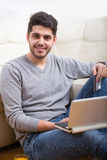 Handsome man holding credit card and using laptop for online shopping Royalty Free Stock Photo