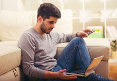Handsome man holding credit card and using laptop stock images