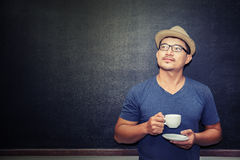 Handsome man holding a cup of coffee standing in front of blackb. ?an holding a cup of coffee standing in front of blackboard thinking some thing Royalty Free Stock Image