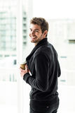 Handsome man holding disposable cup looking back to camera Royalty Free Stock Images