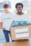 Handsome man holding donation box next to a colleague Stock Images