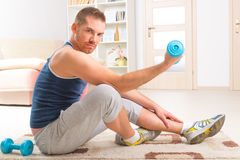 Handsome man holding dumb bells. Happy attractive sporty handsome man doing workouts at home Royalty Free Stock Image
