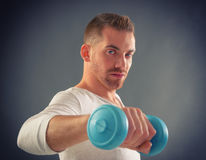 Handsome man holding dumb bells. Happy attractive sporty handsome man doing workouts Royalty Free Stock Image