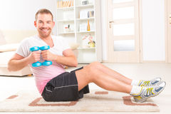 Handsome man holding dumb bells. Happy attractive sporty handsome man doing workouts at home Stock Photo