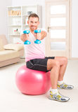 Handsome man holding dumb bells. Happy attractive sporty handsome man doing workouts at home Stock Image