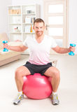 Handsome man holding dumb bells. Happy attractive sporty handsome man doing workouts at home Royalty Free Stock Photography