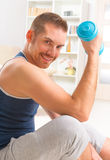 Handsome man holding dumb bells. Happy attractive sporty handsome man doing workouts at home Stock Photos