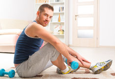 Handsome man holding dumb bells. Happy attractive sporty handsome man doing workouts at home Stock Images
