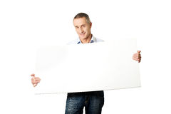 Handsome man holding an empty banner Stock Images