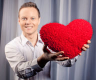 Handsome man holding flower in Valentine day. Focus on heart, other part blurred Stock Photos