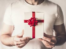 Handsome man holding gift box in hands with red ribbon , close up. Valentines day concept Royalty Free Stock Images