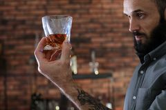 Handsome man holding glass of whiskey royalty free stock photography