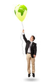 Handsome man holding a green globe balloon Stock Photos