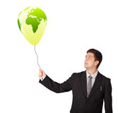 Handsome man holding a green globe balloon Royalty Free Stock Images