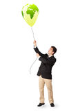 Handsome man holding a green globe balloon Stock Photo