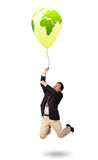 Handsome man holding a green globe balloon Stock Images