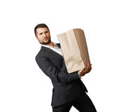 Handsome man holding heavy paper bag Stock Photo