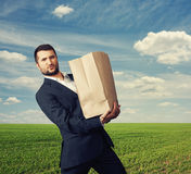 Handsome man holding heavy paper bag Royalty Free Stock Image