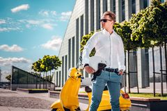 Handsome man holding a helmet and looking sideways standing next to a scooter at the street. Stylishly dressed man holding a helmet and looking sideways standing royalty free stock images