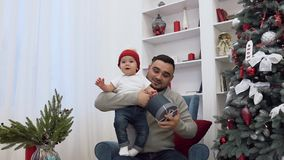 Handsome man holding in his hands funny little baby and showing him beautiful present ,sitting in the chair near stock video