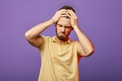 Handsome man holding his head . he has done many mistakes stock photography