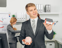Handsome man holding house and piggybank Royalty Free Stock Images