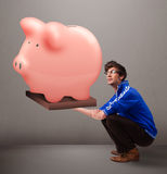 Handsome man holding a huge savings piggy bank Stock Photo