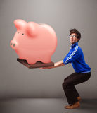 Handsome man holding a huge savings piggy bank Stock Images