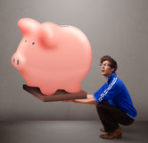 Handsome man holding a huge savings piggy bank. Handsome young man holding a huge savings piggy bank Stock Photography