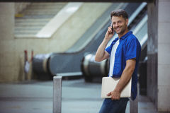 Handsome man holding laptop and talking on mobile phone Royalty Free Stock Photo
