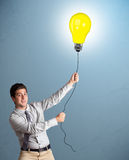 Handsome man holding light bulb balloon Royalty Free Stock Image