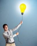 Handsome man holding light bulb balloon Royalty Free Stock Image