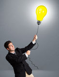 Handsome man holding light bulb balloon Royalty Free Stock Photos