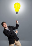 Handsome man holding light bulb balloon Royalty Free Stock Photography