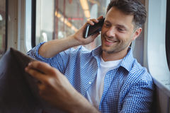 Handsome man holding newspaper while talking on mobile phone Stock Photo