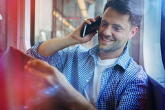 Handsome man holding newspaper while talking on mobile phone Stock Photos