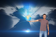 Handsome man holding out a globe Royalty Free Stock Photo