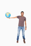 Handsome man holding out a globe Royalty Free Stock Photography