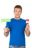 Handsome man holding paint brush and roller. Royalty Free Stock Photography