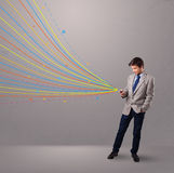 Handsome man holding a phone with colorful abstract lines Stock Image