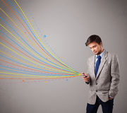 Handsome man holding a phone with colorful abstract lines Stock Images