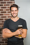 Handsome man holding a pint of beer. In a pub stock photography