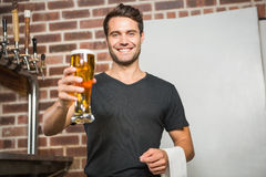 Handsome man holding a pint of beer. In a pub royalty free stock image
