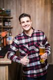 Handsome man holding a pint of beer with thumbs up at caunter in a pub. Handsome man holding a pint of beer with thumbs up in a pub stock photo