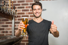 Handsome man holding a pint of beer with thumbs up. In a pub royalty free stock images