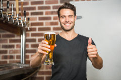 Handsome man holding a pint of beer with thumbs up. In a pub stock image
