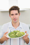 Handsome man holding a plate of broccoli in kitchen Stock Image